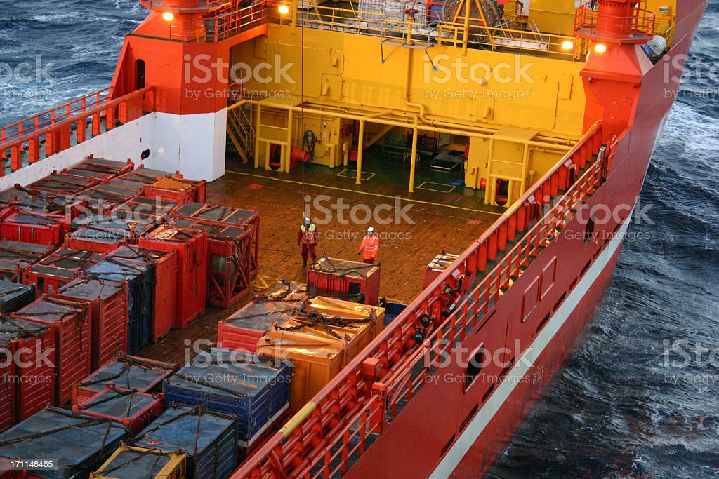 oil rig supply boat men working on deck with lifts stock photo