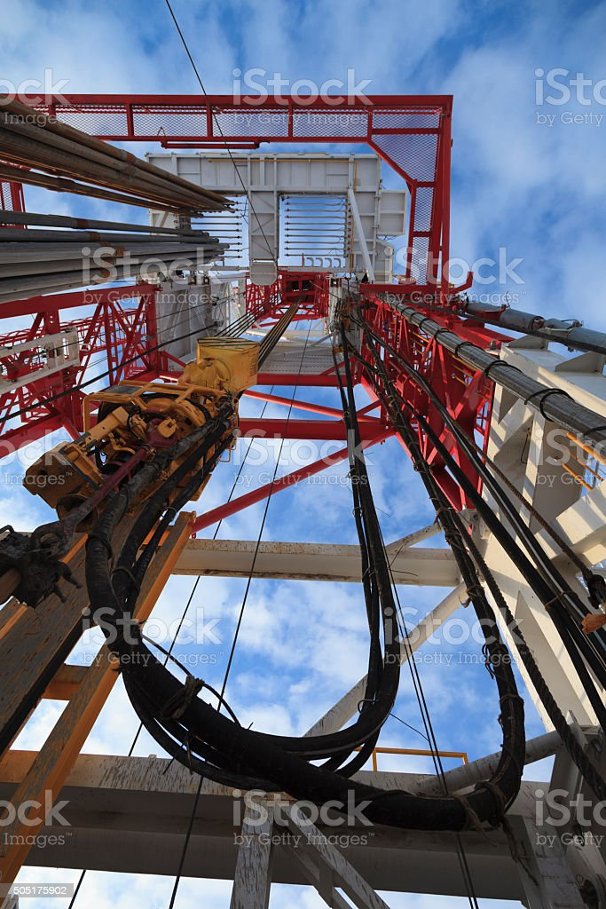 Oil rig view with Top Drive, pipes, sky bottom up stock photo