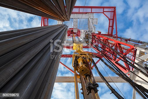 Drilling rig view with Top Drive, many pipes, sky bottom up view in sunny weather in Siberia