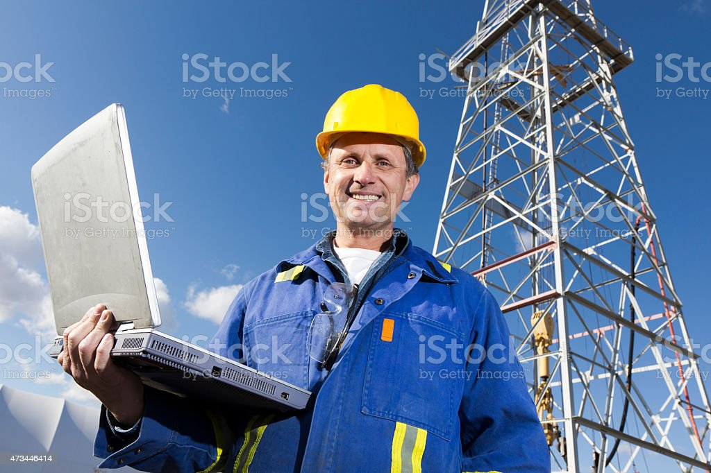 Oil Rig Worker and Laptop stock photo