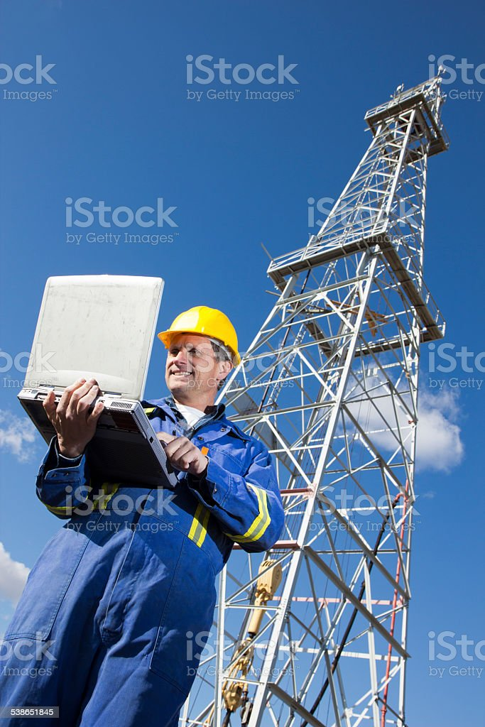 Oil Rig Worker at a Well with Computer Checking Email stock photo