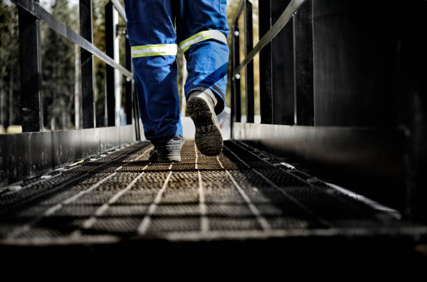 oil rig worker on walkway - crude oil stock photos and pictures