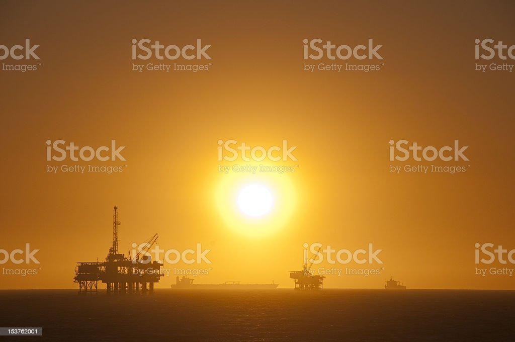 Oil Rigs, ship and Sunset. royalty-free stock photo