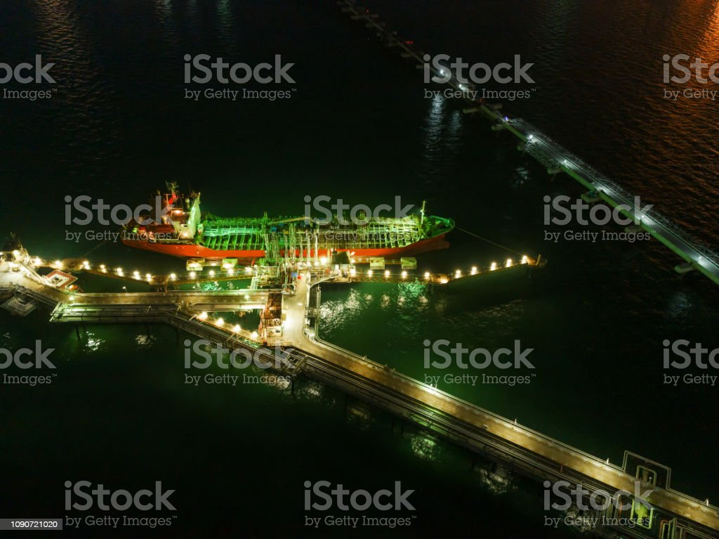 Oil ship tanker loading oil at the oil brige on the sea from refinery...