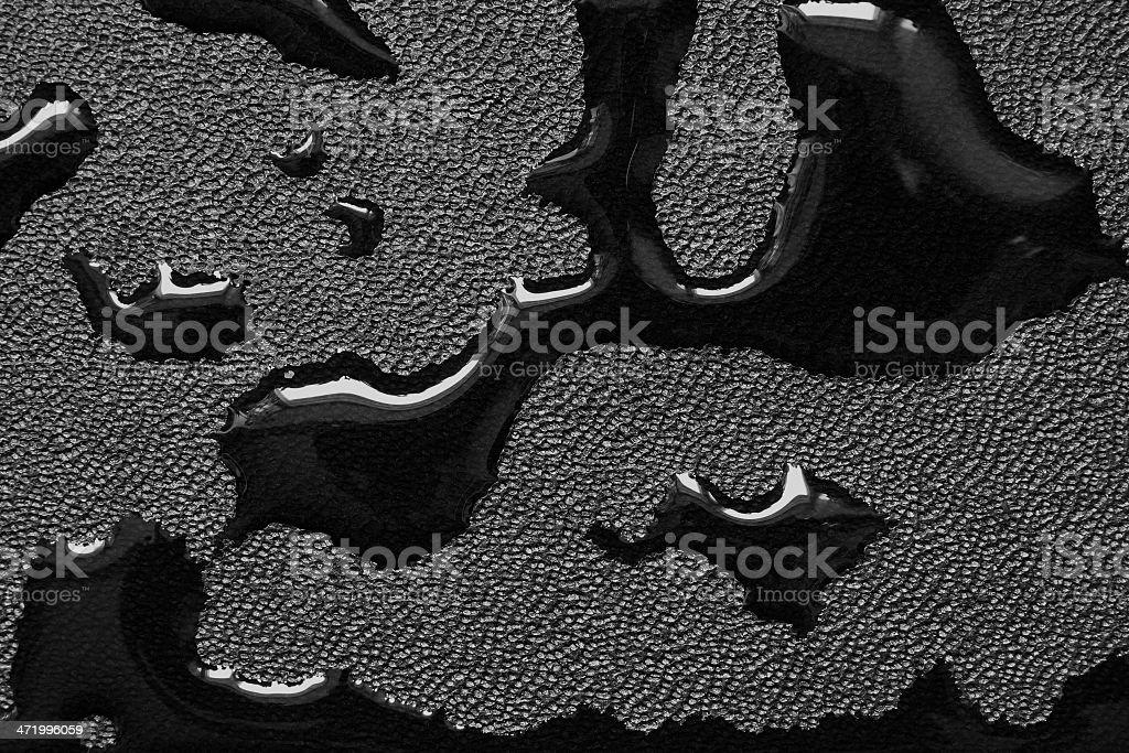 Oil slicks on black leather fabric stock photo