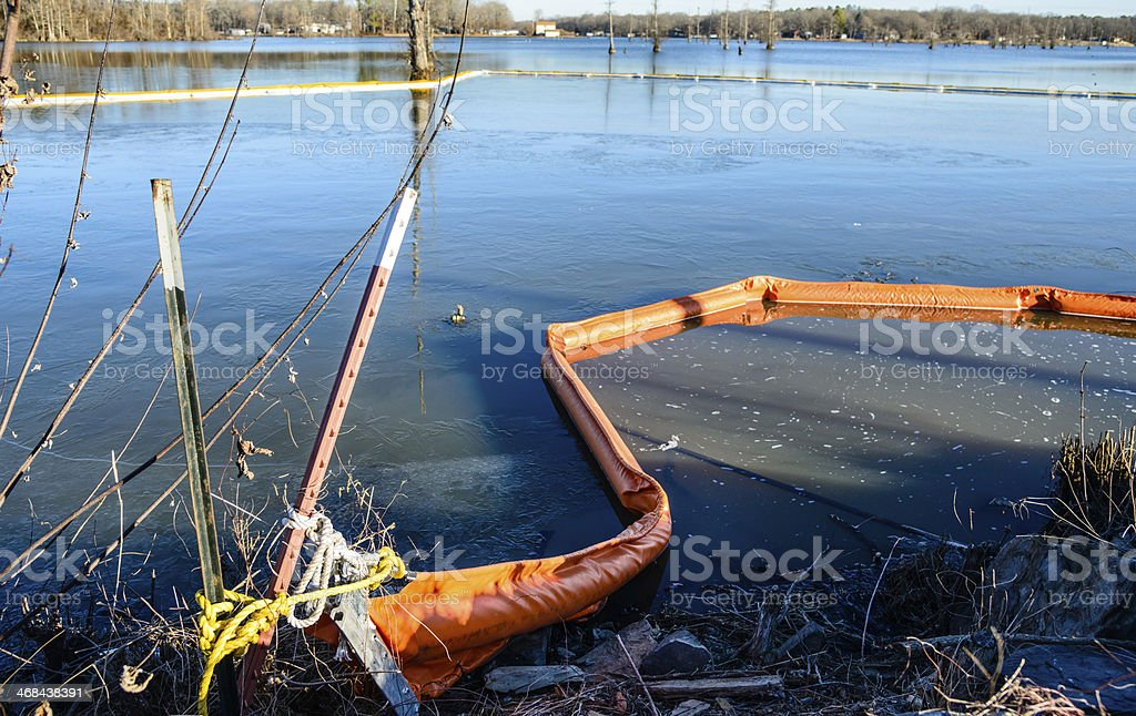 Oil spill containment boom tied to lake bank stock photo