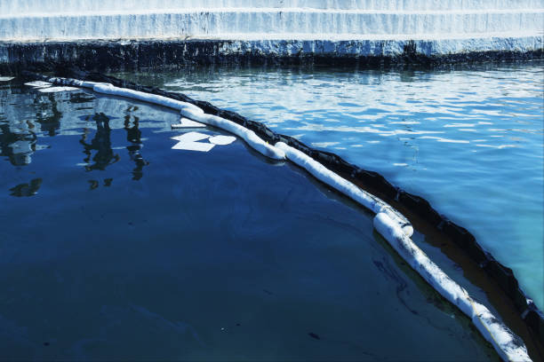 Oil spill. Environmental disaster. A containment boom is a temporary floating barrier used to contain an oil spill. Oil spill. Environmental disaster. A containment boom is a temporary floating barrier used to contain an oil spill. environmental cleanup stock pictures, royalty-free photos & images
