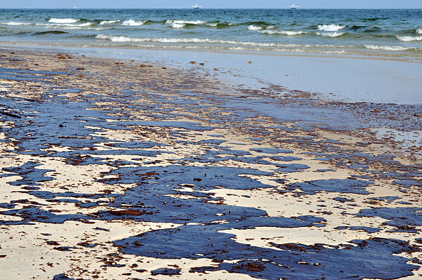 Oil Spill on Beach Oil spill on beach with oil skimmers in background. environmental cleanup stock pictures, royalty-free photos & images