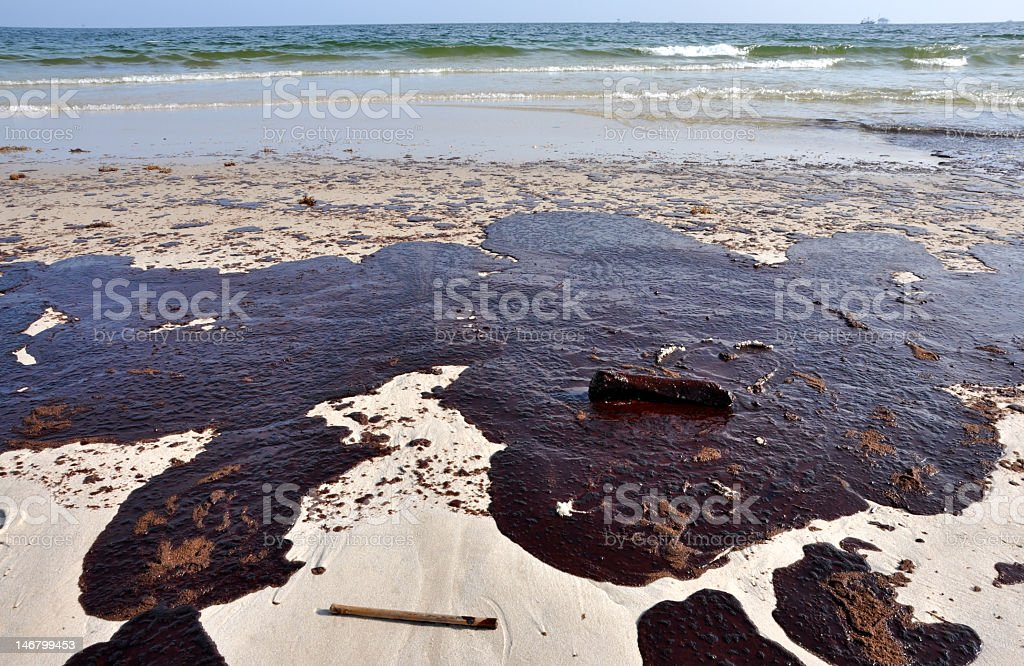 Oil spilled on sandy beach near water stock photo