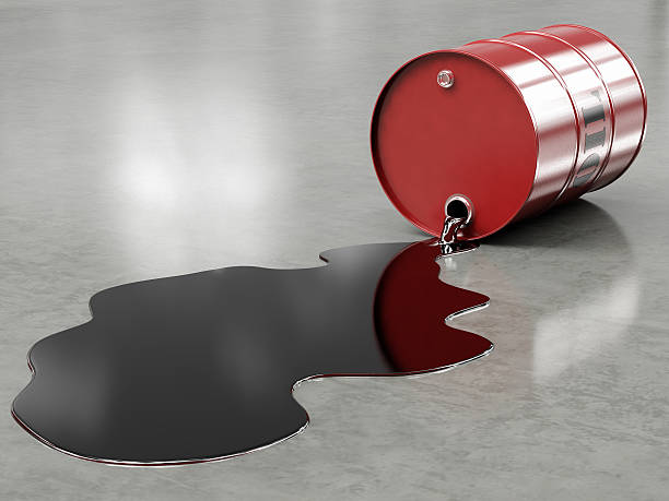 Oil spilling from red barrel onto floor stock photo