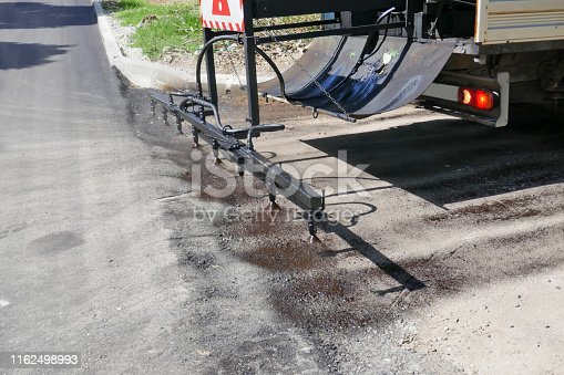 Oil spreader truck applying tack coats spraying bitumen emulsion with  spray lance before applying a new layer of asphalt