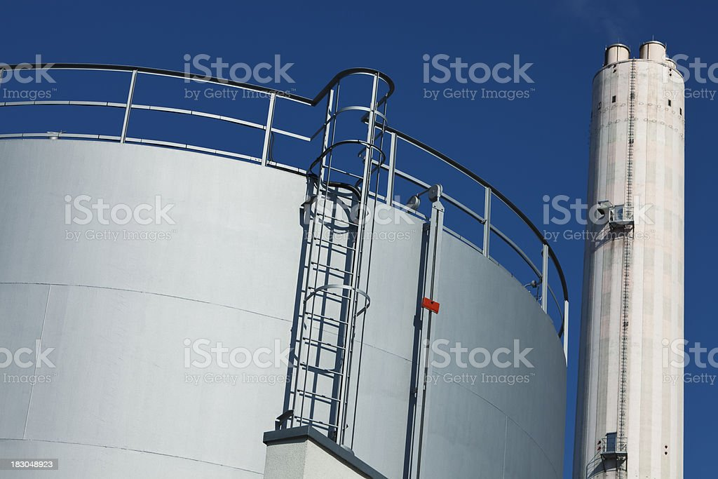 Oil Storage Tank with Ladder and Smoke Stack in Background royalty-free stock photo