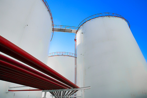 Oil storage tanks in the refinery area and red pipelines