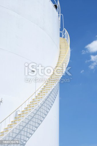 Stairs up an oil refinery storage tank on a sunny day.