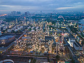 Aerial view morning shot flying at bangkok thailand Oil Refinery Plant Industry of Power Energy and Chemical Petroleum and Manufacturing Petrochemical oil and gas see natural condition of foggy Bang-Krachao and Chao Phraya River in Thailand