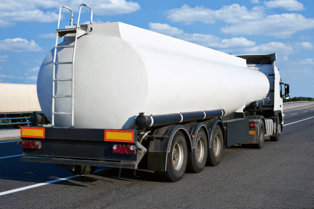 oil truck on road with blank cistern and cloudy sky, cargo transportation concept stock photo