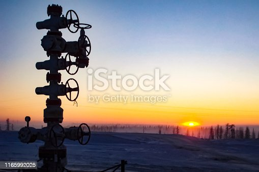 Oil well against the backdrop of a sunset. industrial landscape