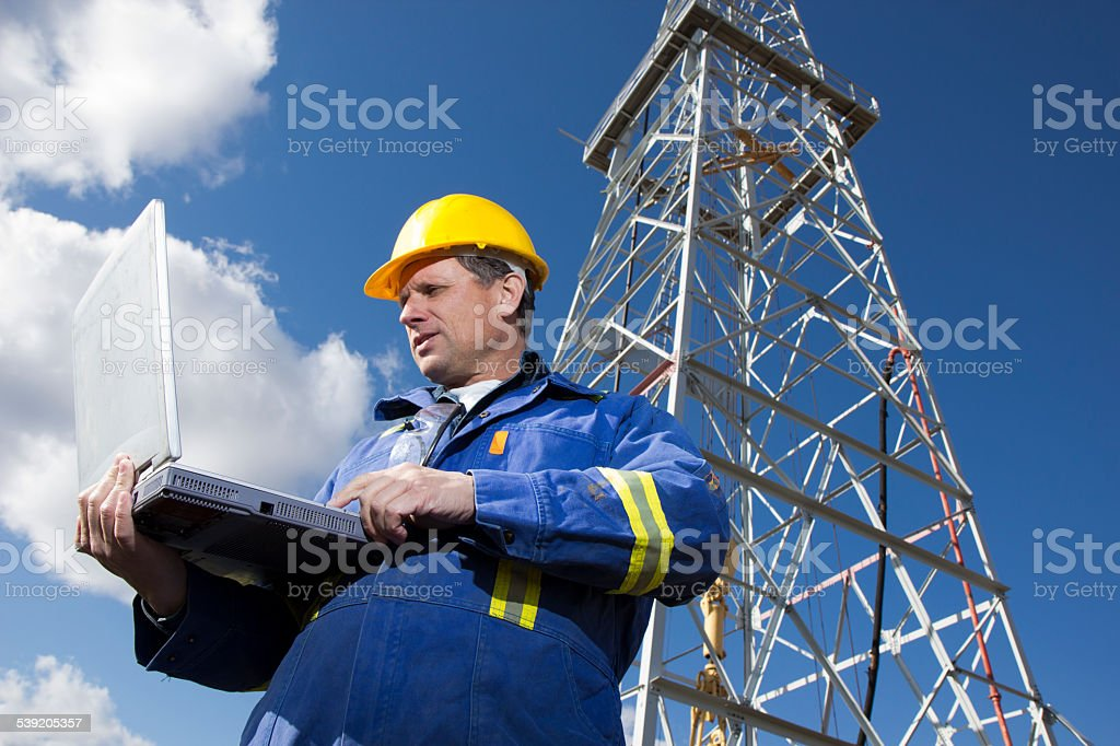 Oil Well Engineer and Computer at a Drilling Rig stock photo