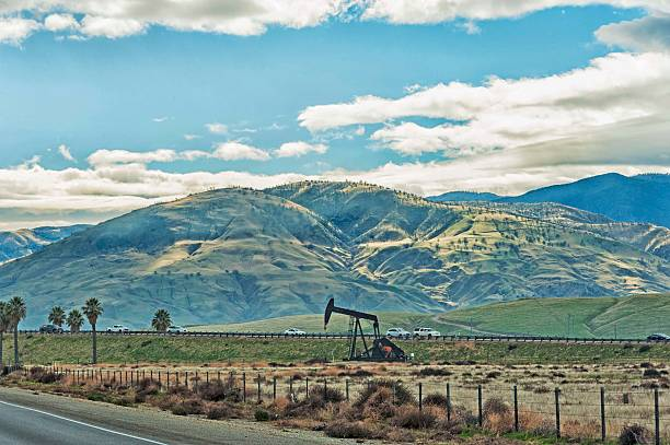 Oil Well Near Bakersfield and Mountains along Highway stock photo