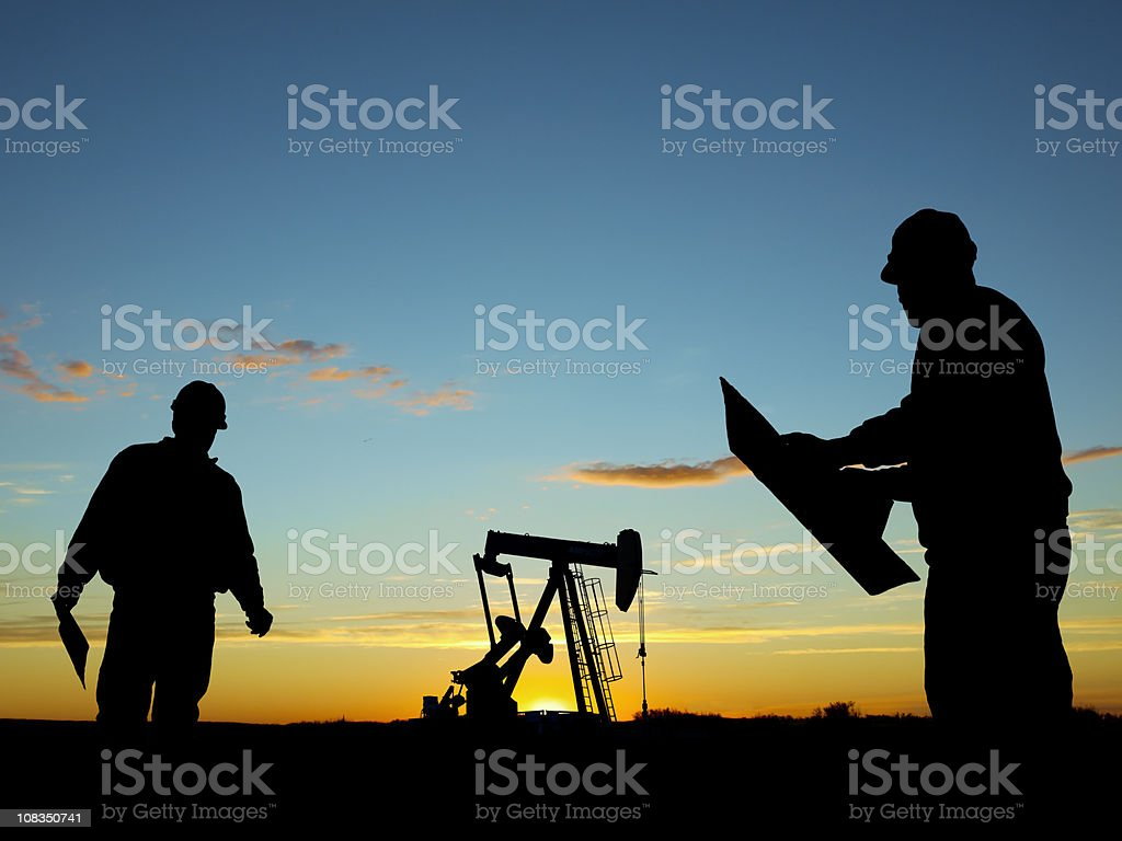 Oil Well Pump Pumpjack & Worker Silhouettes royalty-free stock photo