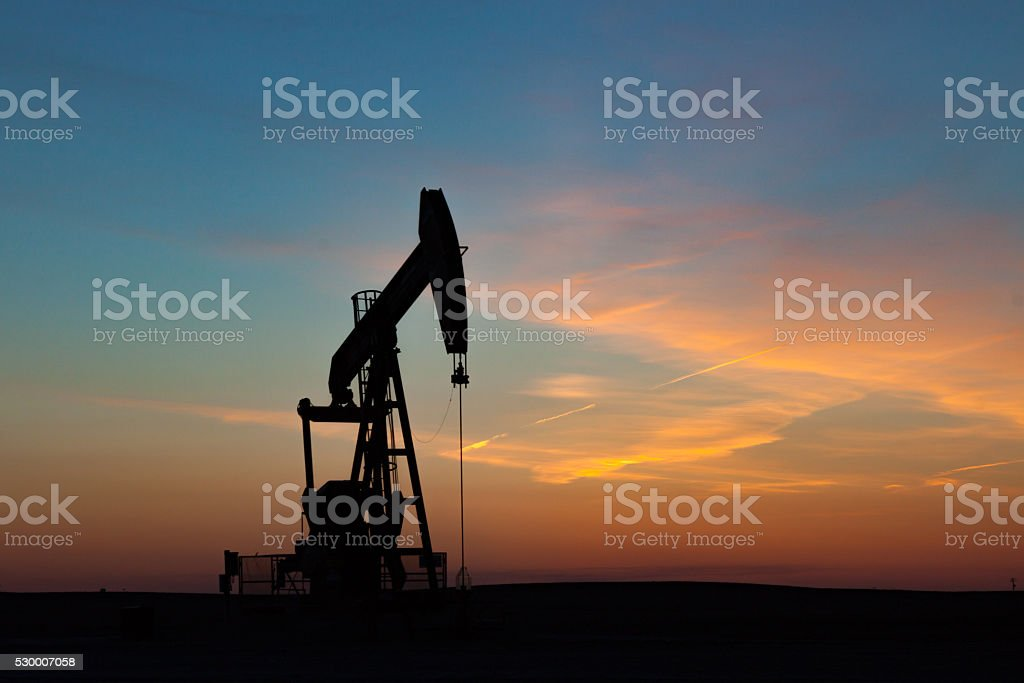 Oil Well Silhouetted Against Prairie Sunset stock photo