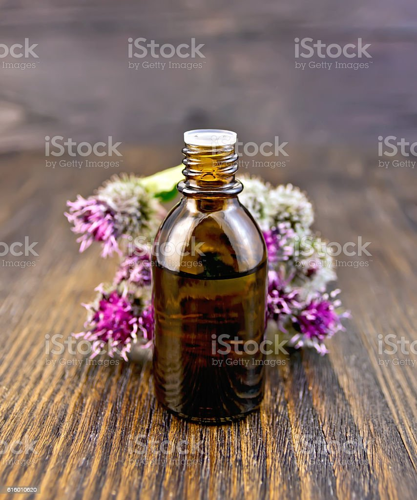 Oil with burdock in vial on board stock photo