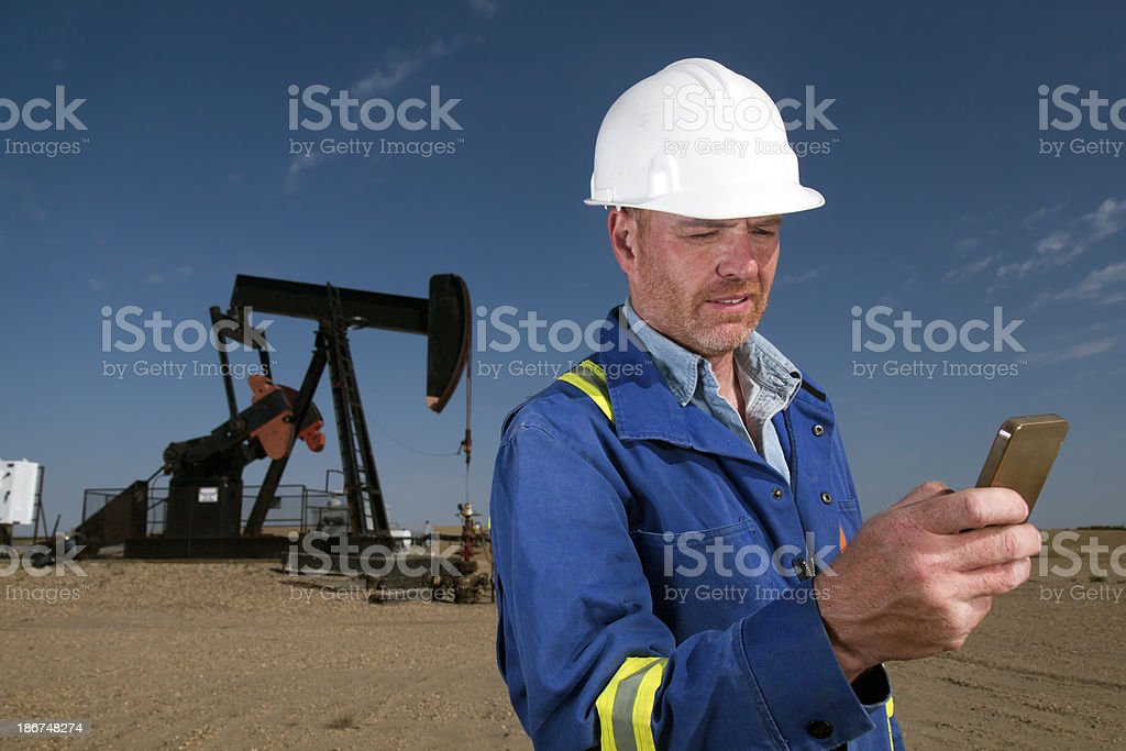 Oil Worker Checking Phone royalty-free stock photo