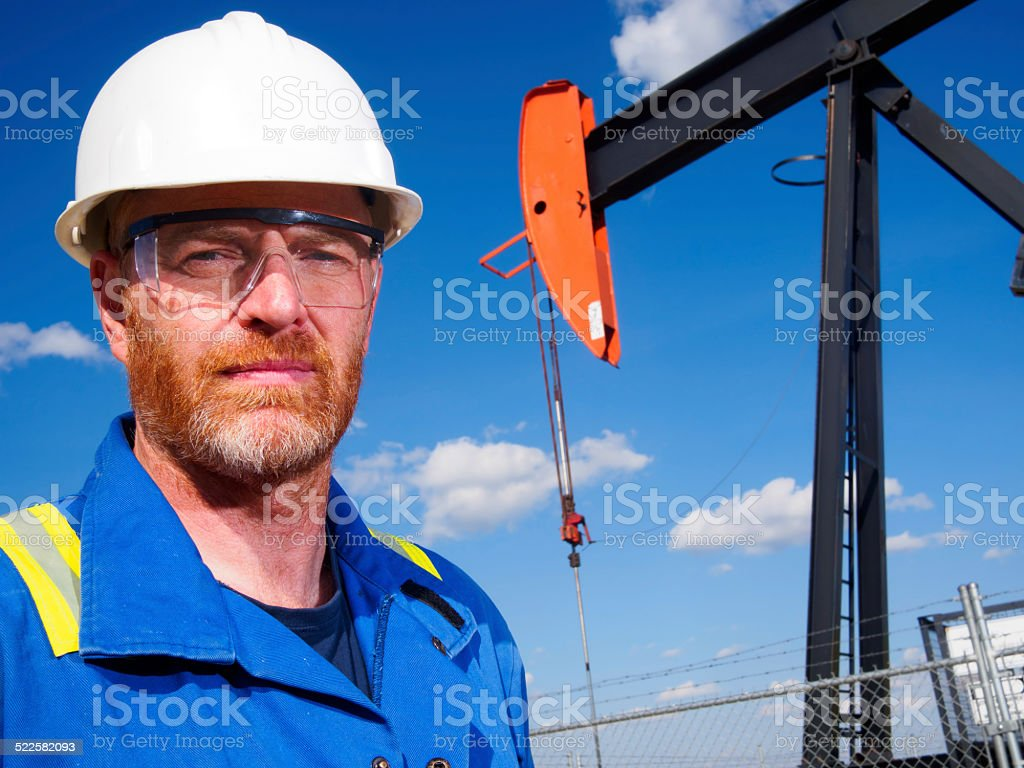 Oil Worker in front of an Oil Pumpjack stock photo