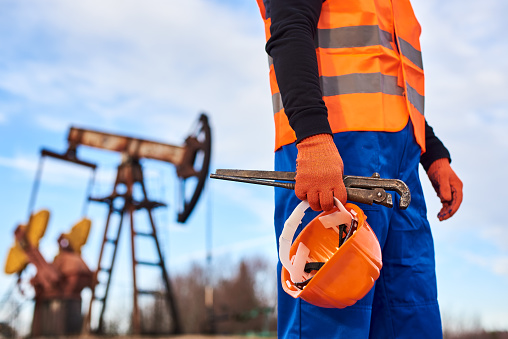 Cropped close-up snapshot of a man wearing blue overalls orange vest and gloves, holding a pipe wrench and a helmet on foreground, oil pump jack on background. Concept of petroleum industry.