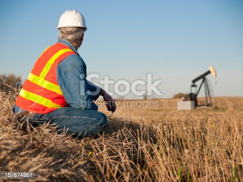 Oil worker engineer, safety inspector at Oil Well pumpjack site during soft morning light.  Central Alberta Canada.