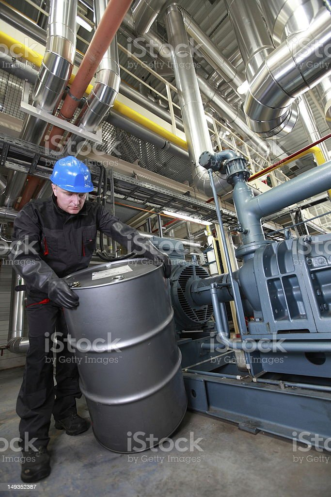 Oil Worker  inside refinery dealing with silver  barrel royalty-free stock photo