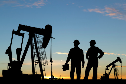An image from the oil industry of two oil workers in conversation against a sunset.