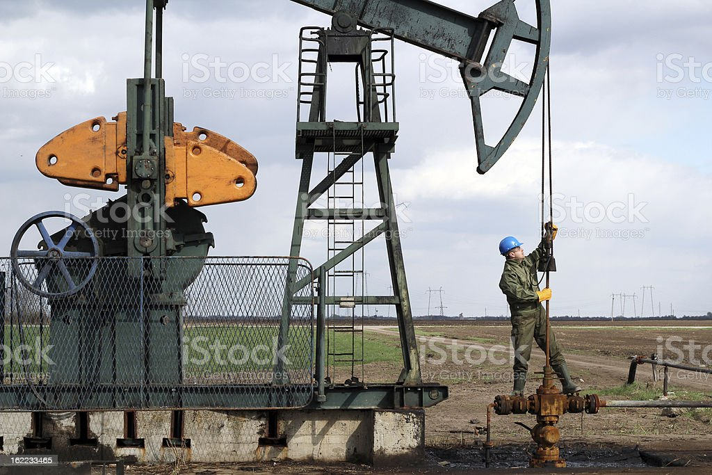 oil worker standing at pipeline stock photo