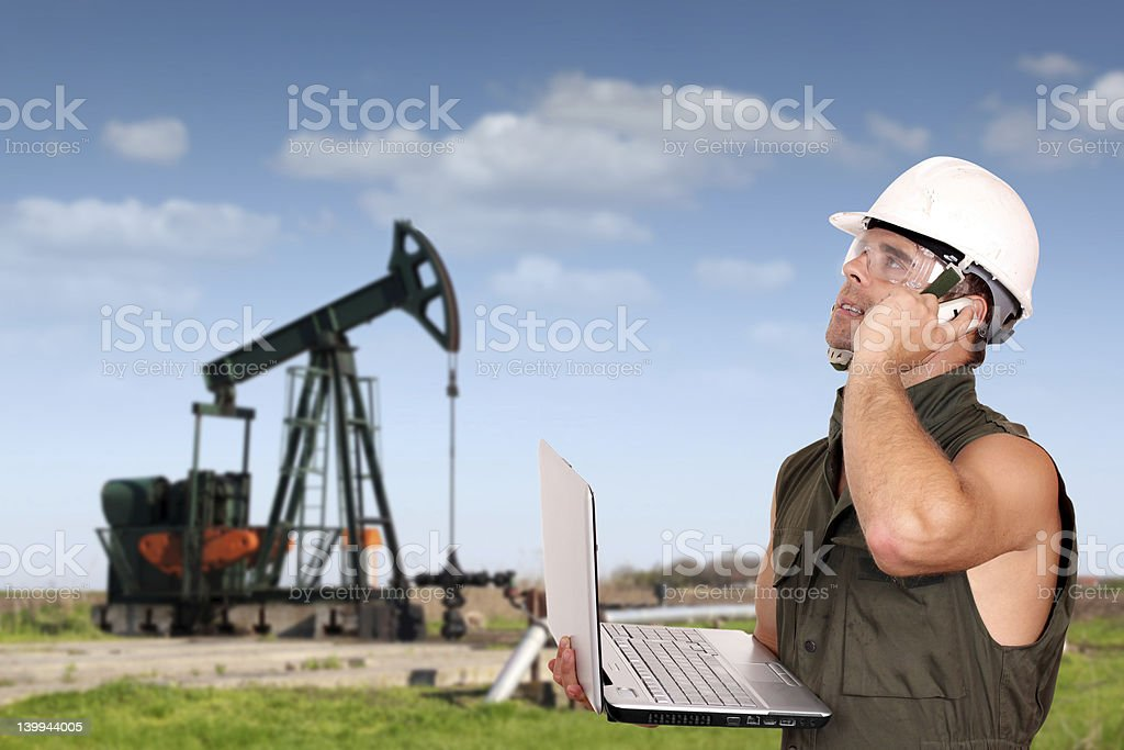 oil worker with laptop and phone royalty-free stock photo
