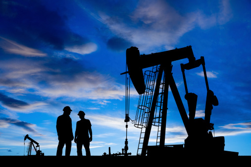 A royalty free image from the oil and gas industry of two oil workers in an oil field at dusk.