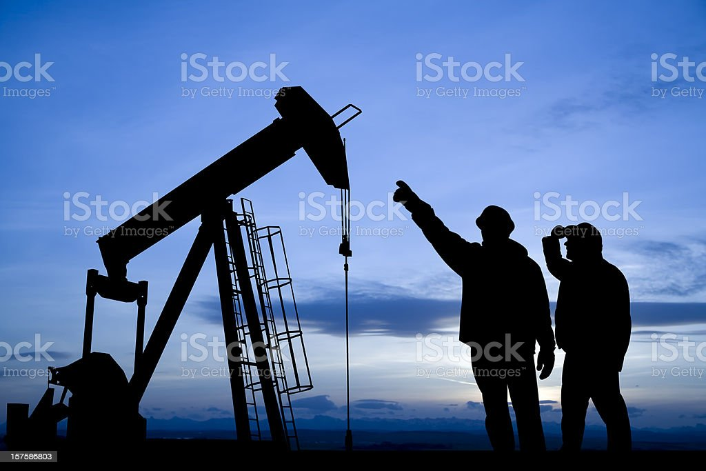 Oil Workers Inspecting a Pump Jack royalty-free stock photo