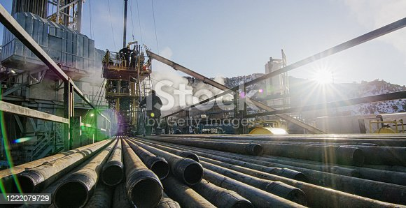 Oilfield Workers Rig Up Drilling Pipe an Oil and Gas Drilling Pad Site on a Cold, Winter Morning