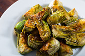 Delicious oil-fried cut artichokes served on plate. Healthy food