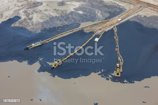 Crude oil seen separated from sand for collection. Tailings ponds are used to separate the heavy oil bitumen from the sticky sand mined from around the area.  Near Fort McMurray, Alberta.