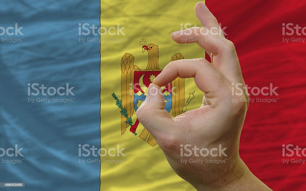 ok gesture in front of moldavia national flag stock photo