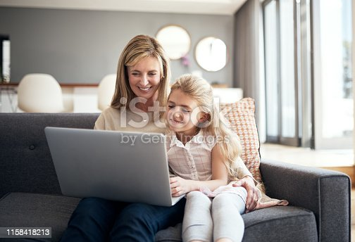 Cropped shot of an attractive mature woman and granddaughter using a laptop while sitting on the sofa at home