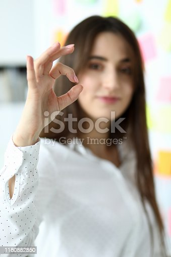 Portrait of pretty female manager standing and showing approving gesture to friendly colleague. Creator looking at camera with gladness. Blurred background