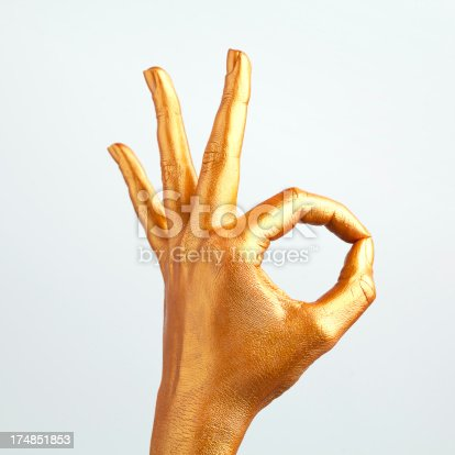 gold painted hand making ok sign