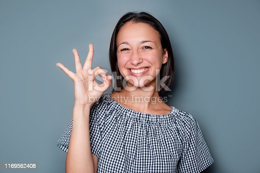 It's ok gesturing woman isolated on gray background