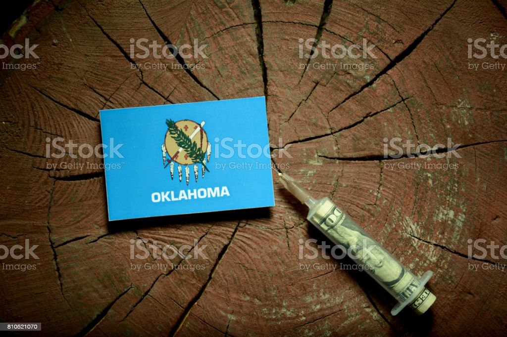 Oklahoma flag on a stump with syringe injecting money in flag stock photo
