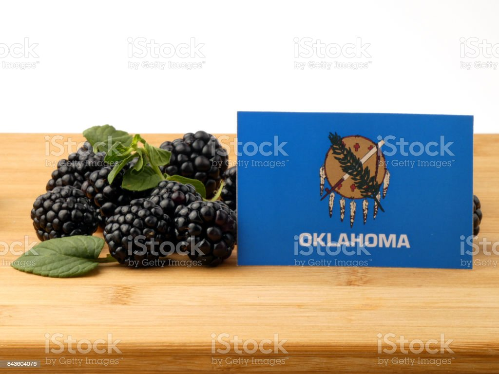 Oklahoma flag on a wooden panel with blackberries isolated on a white background stock photo