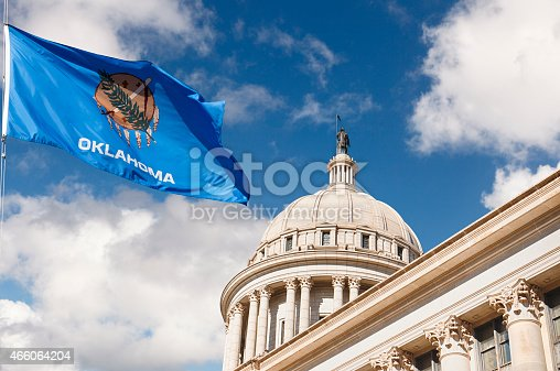 State Capitol Building in Oklahoma City with US state flag outside on a partly cloudy day