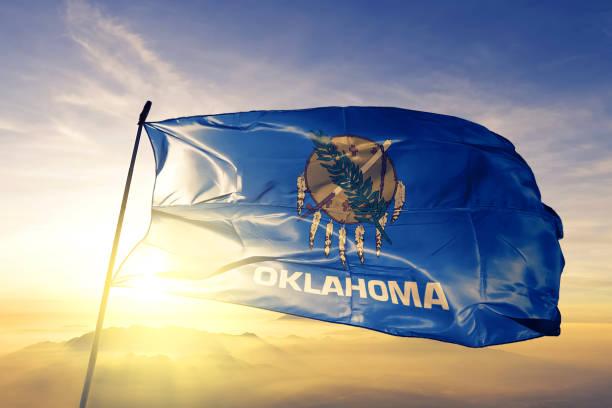 Oklahoma state of United States flag textile cloth fabric waving on the top sunrise mist fog stock photo