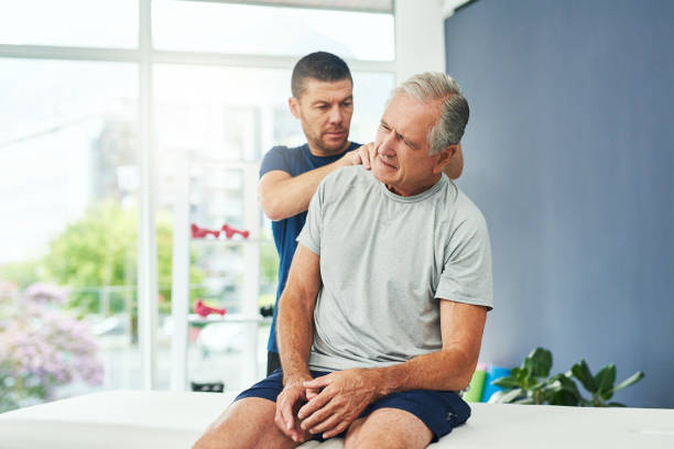 Ok...let's see here Cropped shot of a handsome young male physiotherapist doing a consultation and assessment with a senior patient human neck stock pictures, royalty-free photos & images