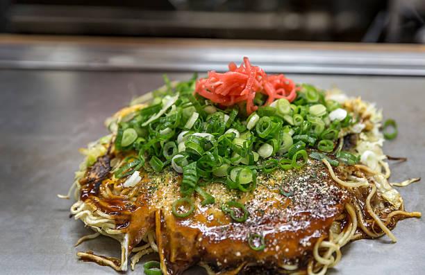 pizza hin zur einheimischen spezialität okonomiyaki japanische - teppan yaki grill stock-fotos und bilder
